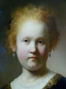RembrandtCloseupPortraitOfAGirlWearingAGoldTrimmedCloak